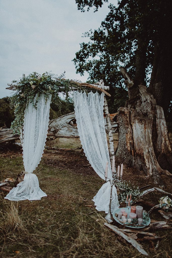 a very simple rustic fall wedding arch of branches, eucalyptus, baby's breath and lace curtains plus candles around is amazing