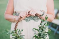 a vine hoop wedding bouquet with lush greenery, white blooms is a pretty idea for a spring or summer wedding
