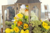 a vintage wedding centerpiece of a vintage candle lantern filled with sunflowers, yellow tulips, billy balls, white and blush roses and candles around