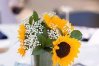 a wedding centerpiece of sunflowers, foliage and baby's breath in a glass is a simple and cool idea for a rustic wedding