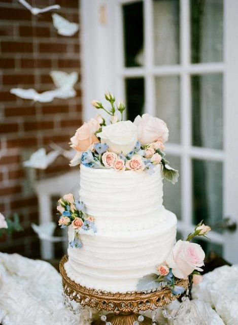 a white textural wedding cake topped with pink and blue flowers and leaves is a stylish and chic idea for a spring or summer wedding