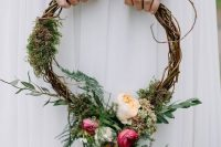 a woodland hoop wedding bouquet of vine, moss, greenery, peachy and pink blooms is a pretty idea for a woodland wedding