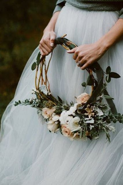 a woodland hoop wedding bouquet with greenery, white and pastel blooms and with green ribbons is a very beautiful idea