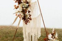 an amazing boho fall wedding arch with macrame, white and peachy blooms, dried leaves, pampas grass and dried fronds