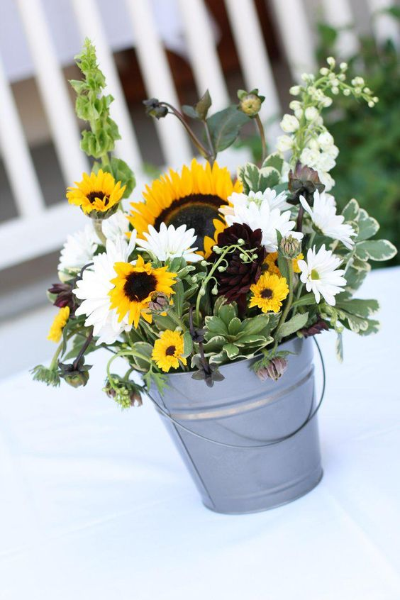 an amazing fall wedding centerpiece in a bucket,w ith sunflowers, white gerberas, greenery and some dark blooms