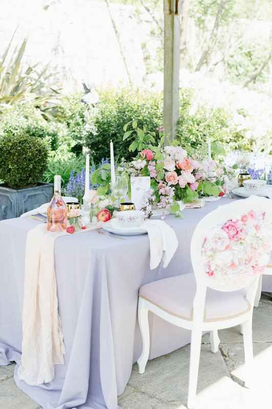 an elegant English garden wedding tablescape with a lilac tablecloth and neutral napkins, a chic peachy and pink rose centerpiece, tall candles and peaches on the table
