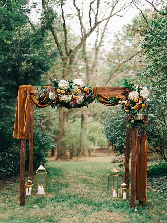an elegant and refined rustic fall wedding arch with mustard velvet, white, yellow, burgundy blooms and greenery is a very stylish and cool idea