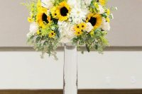 an elegant colorful wedding centerpiece of greenery, billy balls, sunflowers, white roses and other blooms in a tall glass vase