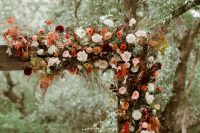 an elegant rustic fall wedding arch detailed with blush, red, rust, orange, burgundy blooms, greenery and bright fall foliage