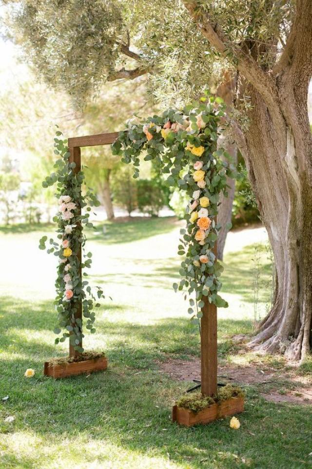 an elegant rustic fall wedding arch with eucalyptus, peachy, white and yellow roses and moss at the base is a cool and stylish solution
