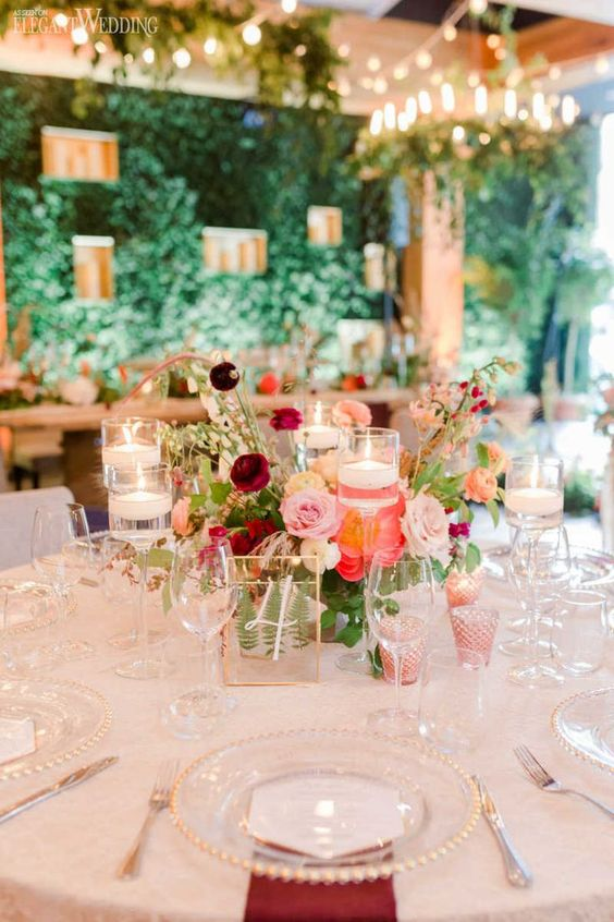 an elegant secret garden wedding table setting with bold blooms and greenery, floating candles, burgundy napkins and gold edge plates