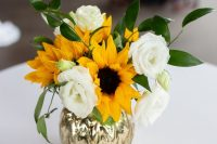 an elegant wedding centerpiece of sunflowers, white roses and greenery in a mercury glass vase is a gorgeous idea for summer or fall