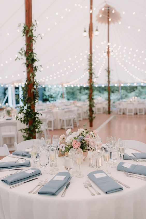 an elegant wedding tablescape with blue napkins, a pink, white and blue floral centerpiece and some glasses is a very chic idea