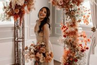 an incredible bright boho fall wedding arch with rust-colored and pink and blush roses, white orchids, pampas grass, rust-colored fall foliage just excites