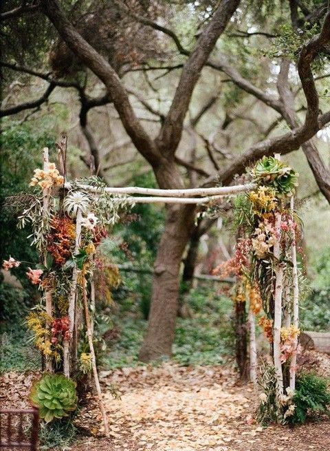 an unusual boho rustic wedding arch of branches, greenery, dried fall leaves, air plants, succulents is a very fresh and bold idea for the fall
