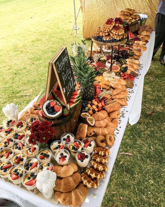 a wedding brunch bar with parfait, croissants, waffles, fresh fruits, berries and sauces plus chalkboard signs marking what's in here