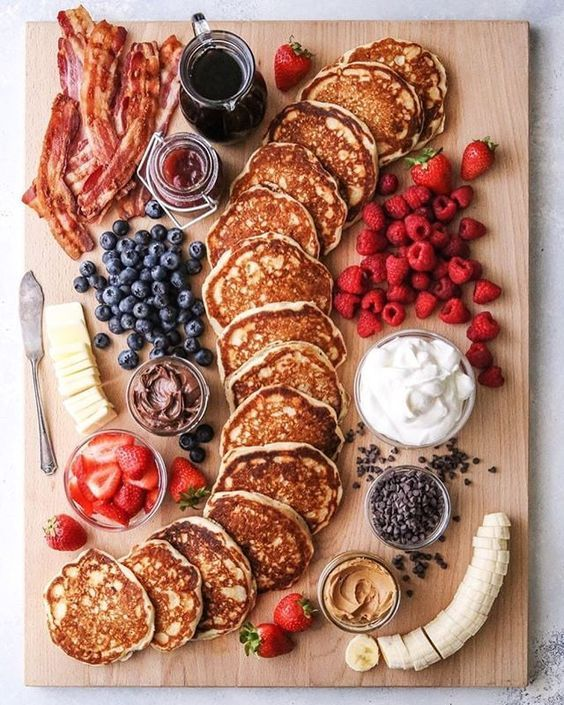 a charcuterie board for a brunch wedding, with pancakes, berries, cheese, bacon and some fruits and sauces