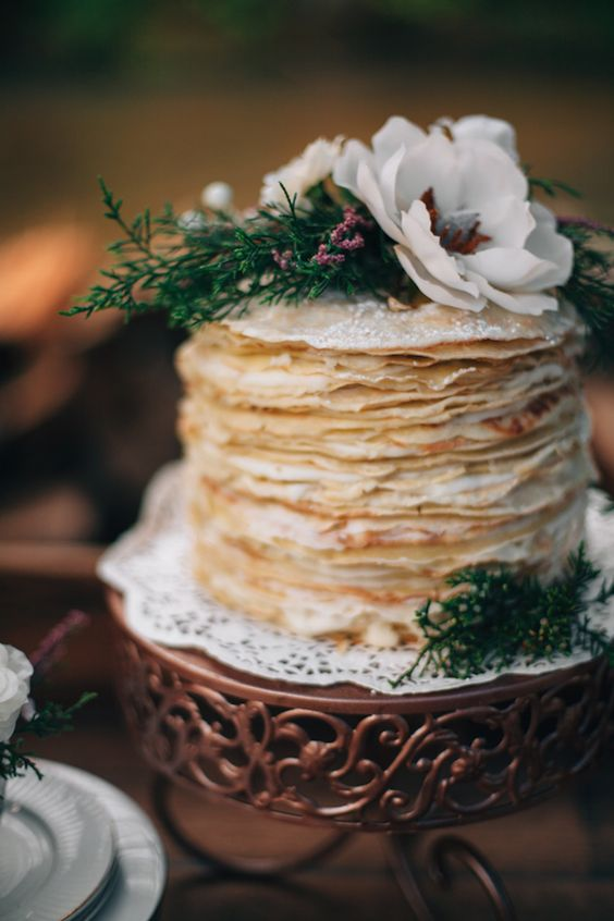 an ethereal crepe wedding cake topped with greenery and white blooms is a very cool and delicious solution