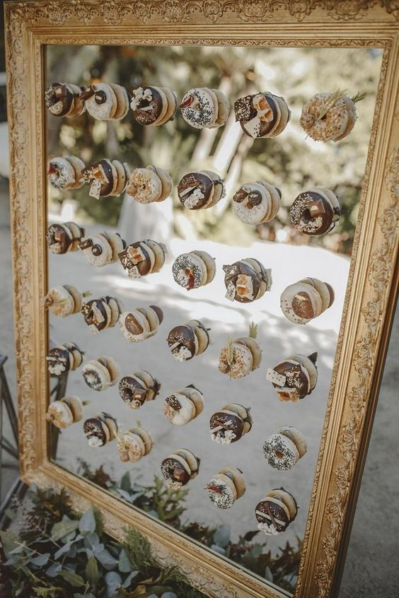 a mirror in a vintage frame with holders for donuts is a very elegant idea that will easily fit a brunch wedding