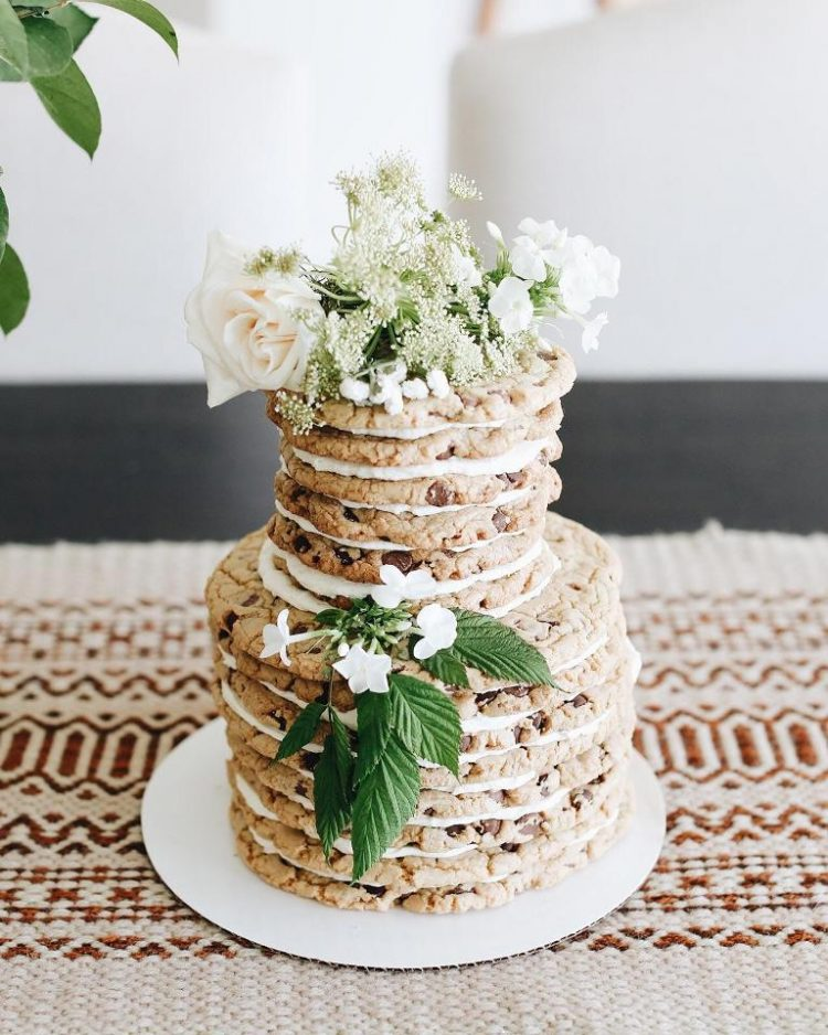 a chocolate chip cookie wedding cake with white blooms, white filling and some foliage looks gorgeous and yummy