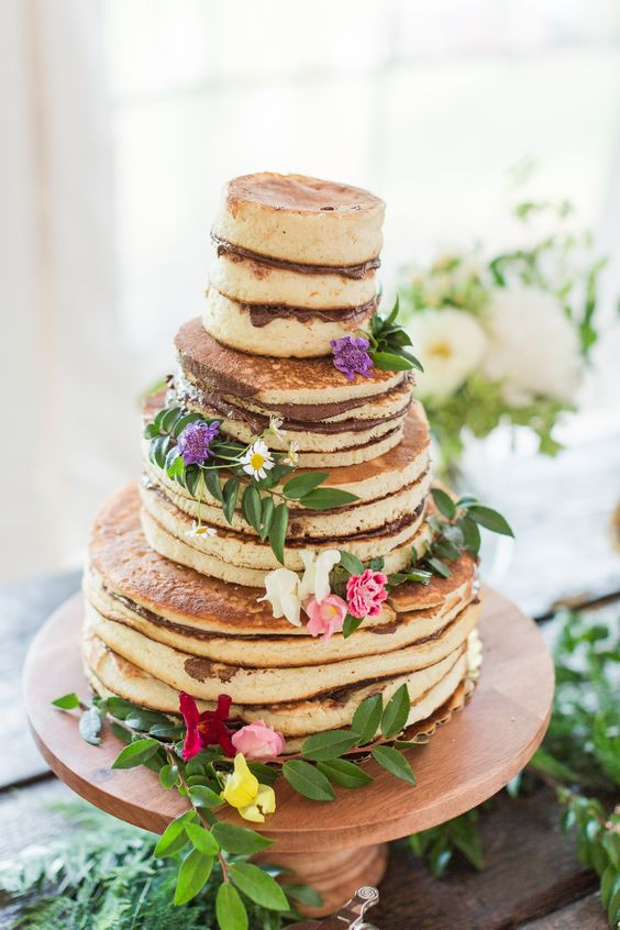 a very simple pancake wedding cake topped with Nutella and topped with fresh blooms and greenery can be easily DIYed