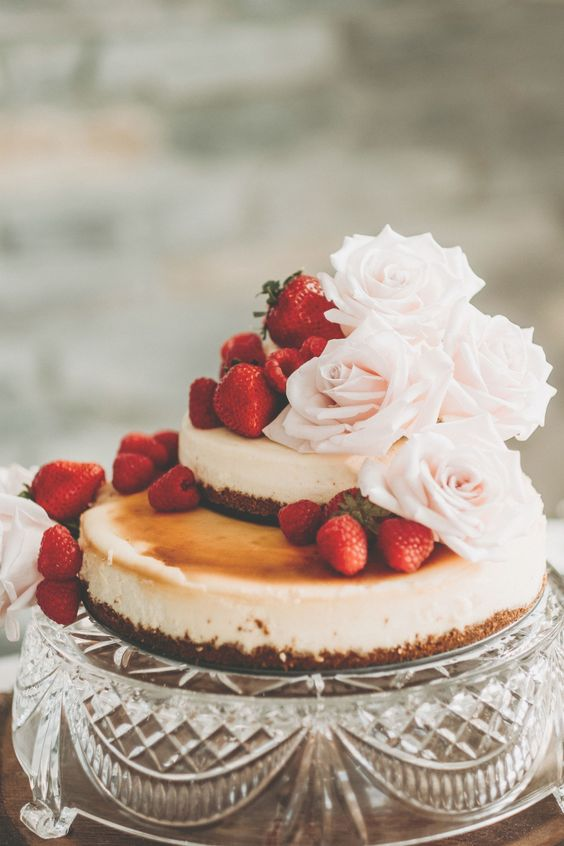 a lovely two-tier wedding cheesecake with fresh strawberries and blush roses is a very beautiful idea to try