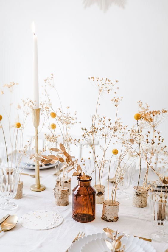 a beautiful and easy cluster wedding centerpiece of billy balls, dried leaves, grasses and candles in tall candlesticks is a pretty rustic idea