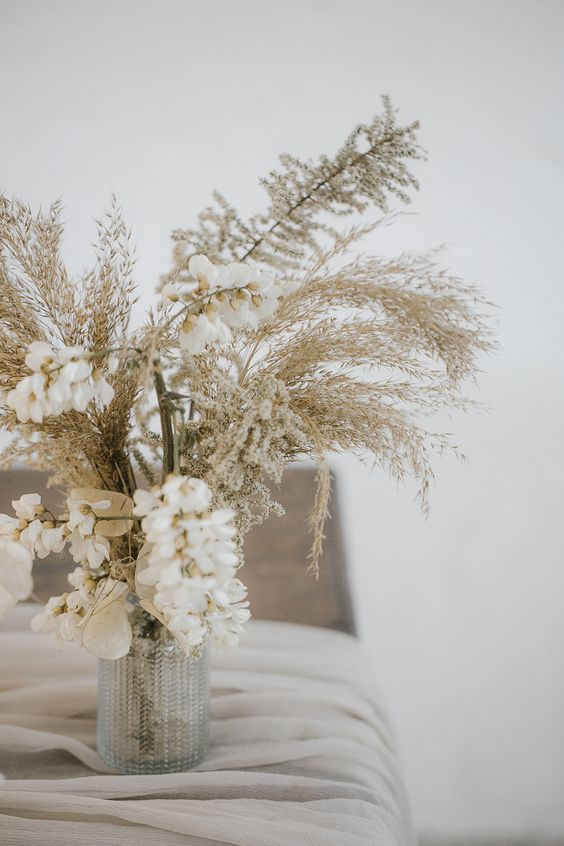 a beautiful and ethereal wedding centerpiece of a vintage vase, some white blooms, lunaria and dried grasses is a lovely idea