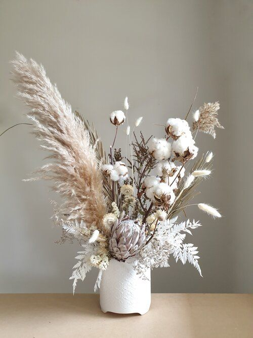 a beautiful and textural wedding centerpiece with cotton, pampas grass, whitewashed leaves, a king protea and bunny tails is amazing
