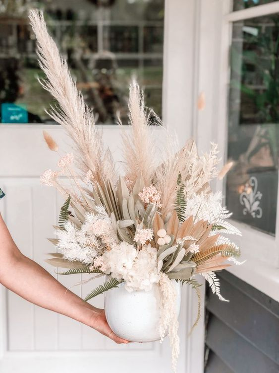 a beautiful dried flower wedding centerpiece of white and pink dried blooms, grasses, leaves and fronds, fern leaves is amazing
