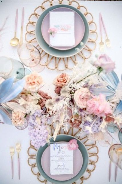 a beautiful iridescent wedding table setting with wooden placemats, bold dried blooms and leaves, pastel plates and pink cutlery is chic