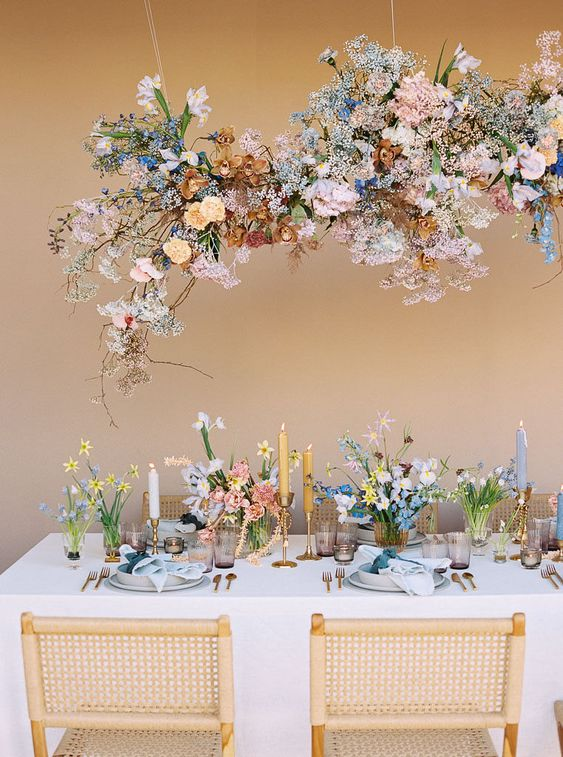 a beautiful iridescent wedding tablescape with pretty blooms over the table and on it, with mustard and blue candles, with blue napkins and elegant cutlery