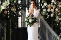 a beautiful mermaid plain wedding dress with a deep neckline and long sleeves plus a train and a cathedral veil for a luxurious wedding