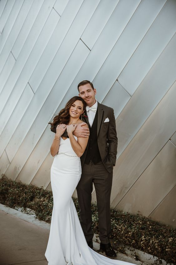 a beautiful modern mermaid plain wedding dress with a V neckline, a train and an embellished belt is amazing
