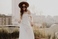 a beautiful modern plain off the shoulder wedding dress paired with a neutral hat and sunglasses is amazing