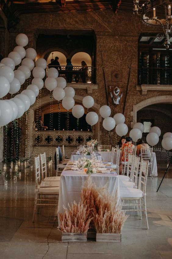 a beautiful wedding reception styled with white balloons, lights, pampas grass and neutral blooms is a very cool idea