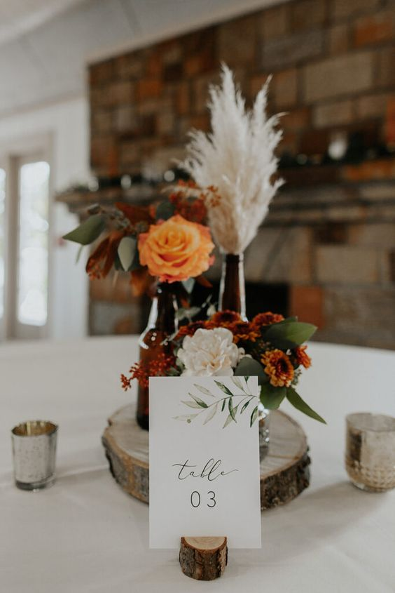 a boho fall wedding centerpiece of a wood slice, neutral and bold blooms, pampas grass, greenery and candles around is amazing for the fall