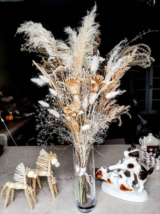 a boho wedding centerpiece of dried blooms, bunny tails, dried grasses is a very bold idea for any summer to fall or fall wedding