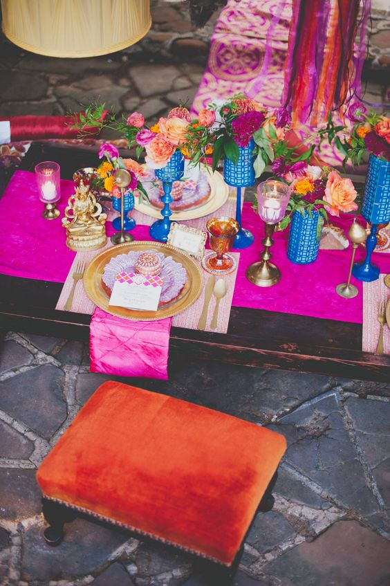 a bold Moroccan bridal shower tablescape with a hot pink table runner, bold candleholders and vases, gold chargers and cutlery, colorful blooms