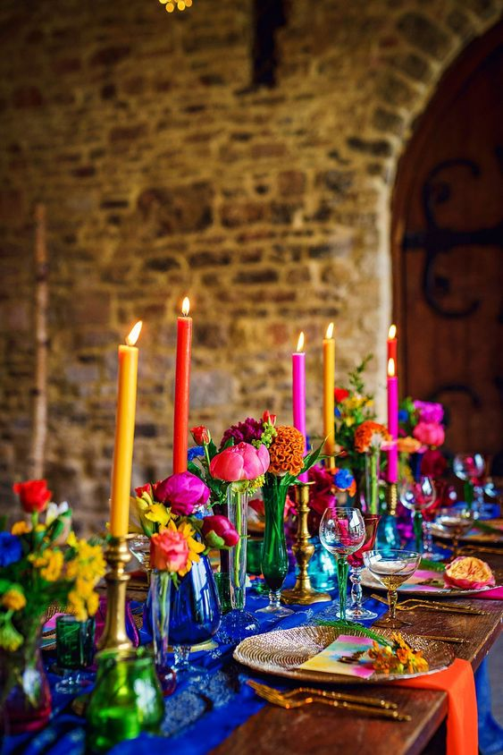 a bold Moroccan bridal shower tablescape with an electric blue table runner and jewel tone vases and candles, colorful napkins is jaw-dropping
