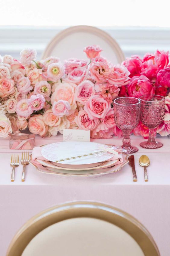 a bold and luxurious bridal shower tablescape with an ombre floral centerpiece, a pink tablecloth, gold cutlery and neutral porcelain