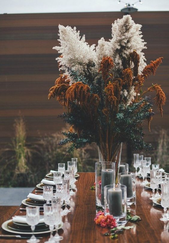 a bold and oversized fall boho wedding centerpiece of pampas grass, greenery and rust blooms, with grey candles around is an amazing idea