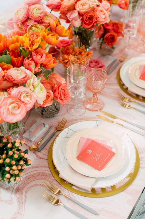 a bold bridal shower tablescape with pink and orange blooms, pink glasses, pink menus and a printed tablecloth, gold cutlery is cool