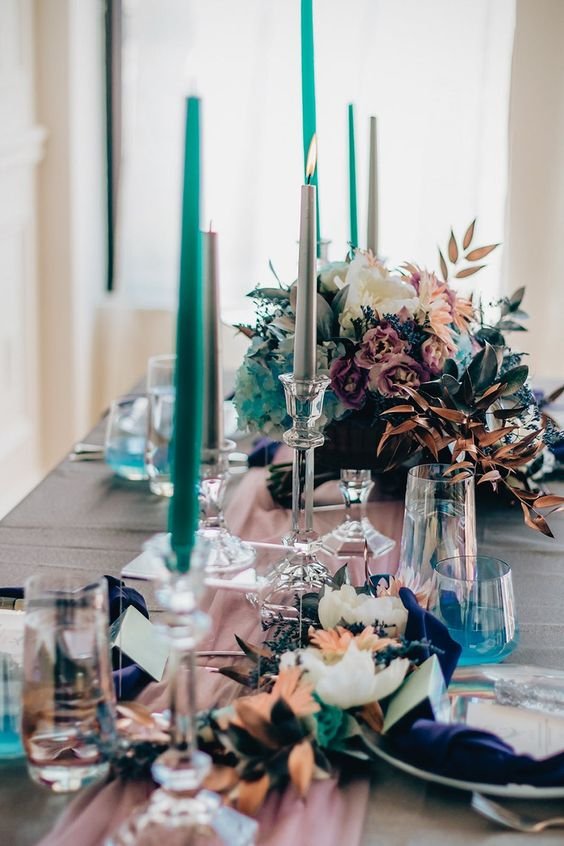 a bold iridescent and holographic wedding tablescape with a pink runner, navy napkins, turquoise candles and iridescent floral arrangements