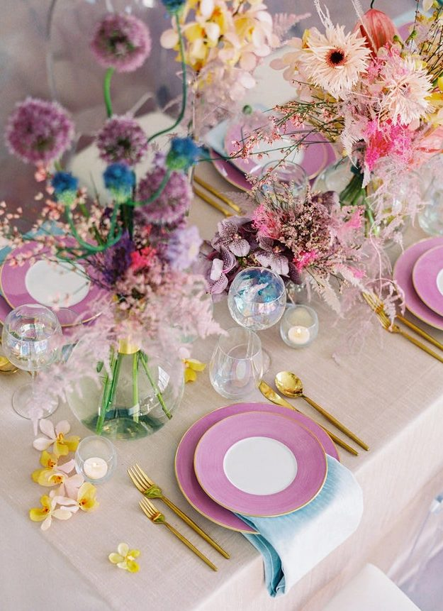 a bold iridescent wedding tablescape with pink, purple, blue, yellow blooms and greenery, purple plates, gold cutlery and candles is amazing