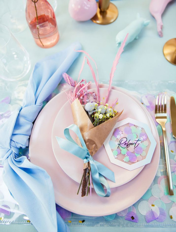 a bright and fun iridescent wedding place setting with blue linens, pink napkins, pink blooms and grasses and a cool card is wow