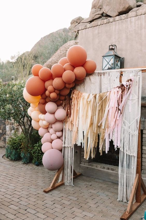 a bright boho wedding arch decorated with macrame, with long and colorful fringe, colorful balloons styled in a color block way