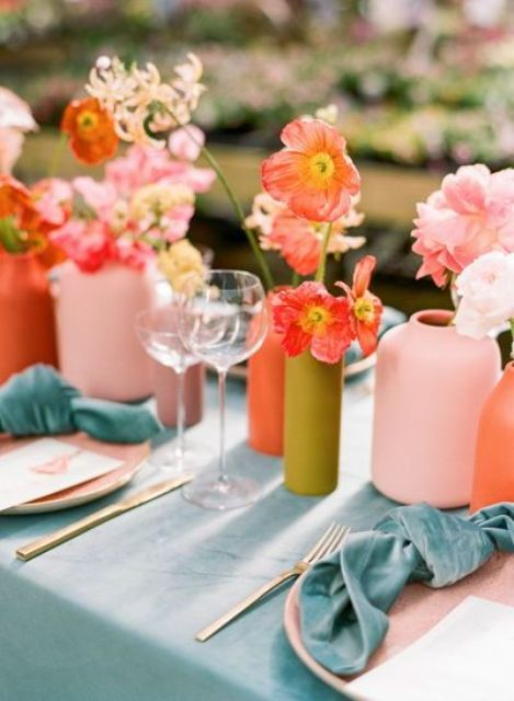a bright bridal shower table setting with muted color vases, pink and red blooms, a blue tablecloth and napkins, pink plates is a chic idea