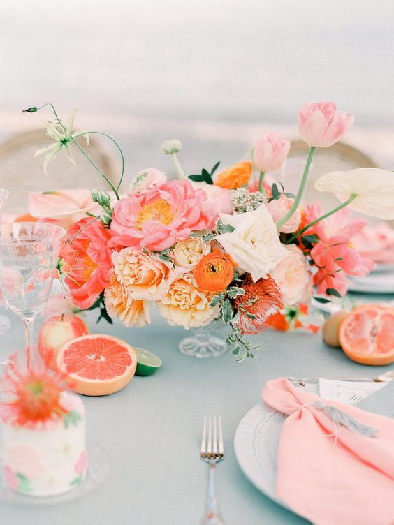 a bright bridal shower tablescape with a blue tablecloth, pink napkins, orange and pink blooms, citrus and floral cakes is a lovely idea