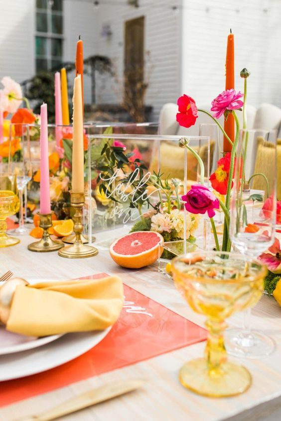 a bright bridal shower tablescape with an orange placemat, bold blooms and candles, colored glasses, citrus slices and mustard napkins